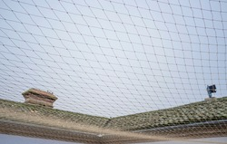 Net covering courtyard area to protect buiding keeping out pest birds. Bird Control Netting concept