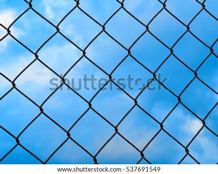 Net metallic pattern barrier against blue sky #537691549