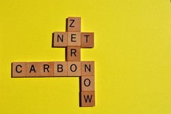 Net, Zero, Carbon, Now, words in wooden alphabet letters in crossword form isolated on yellow background with copy space