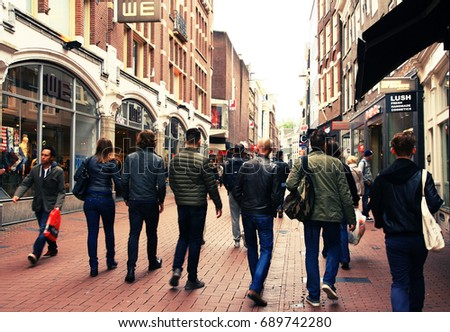 NETHERLANDS. AMSTERDAM - JUNE 23, 2015: Tourists are walking along an old city street in the historic district of the city on a summer day.