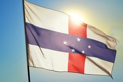 Netherlands Antilles flag waving on the wind in front of sun