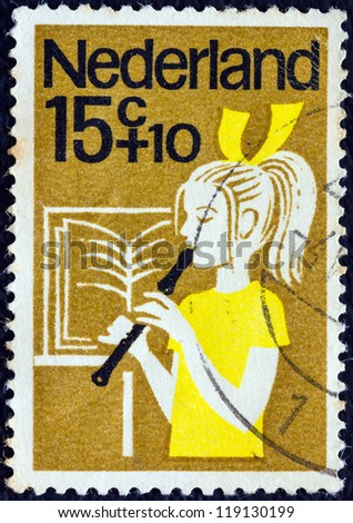 "NETHERLANDS - CIRCA 1964: A stamp printed in the Netherlands from the ""Child Welfare"" issue shows a girl playing the recorder, circa 1964."
