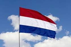 Netherlands flag isolated on the blue sky with clipping path. close up waving flag of Netherlands. flag symbols of Netherlands.