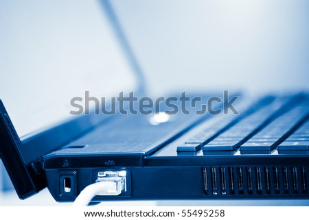 network cable and laptop computer detail with shallow depth of field blue toned