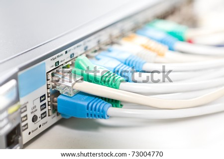 Network cables connected into router, shallow depth of field