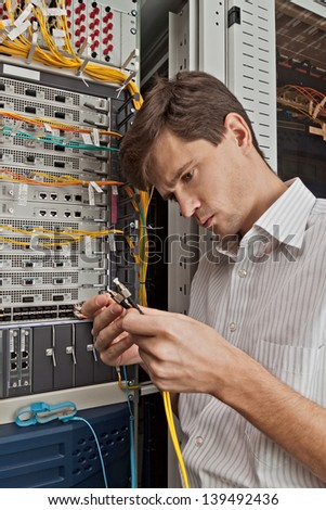 Network engineer in server room with optical patchcord