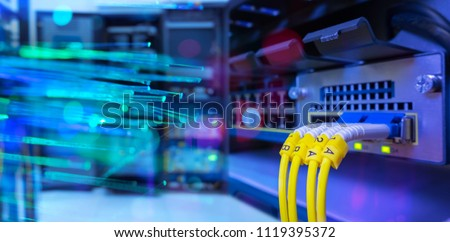 network gigabit switch and fiber optic cable and lighting of fiber optics on background in data center room