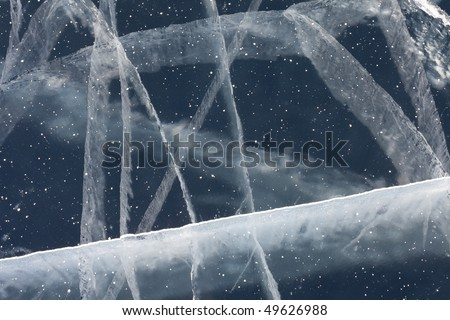 Network of cracks in thick solid layer of ice of a frozen lake due to stress caused by temperature changes.
