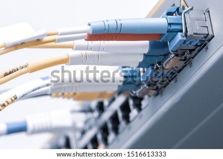Network switch with network ethernet and optical cables close-up with blurred background