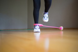 neuro jump rope. child plays sports at home. active lifestyle. activity for kids. feet in sneakers.