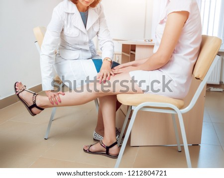 Neurological examination. The neurologist testing reflexes on a female patient using a hammer. Diagnostic, healthcare, medical service