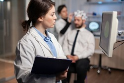 Neurologist scientist looking at brain tomography of patient with headset, high tech scan on monitor screen. Doctor adjunsting electrodes. Modern neuroscience.