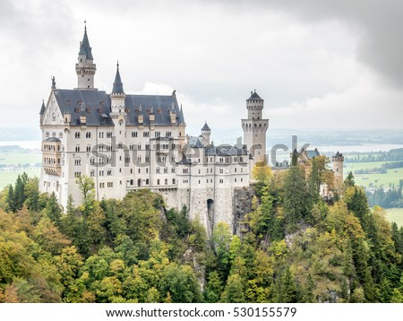 Neuschwanstein castle is the most famous beautiful castle in Germany, inspiration for Disneyland's sleeping beauty castle, located on Alpine foothills, under cloudy sky