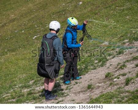 Neustift im Stubai, Tyrol, Austria - July 25, 2018: A paragliding instructor teaches a beginner before take-off at Elfer mountain station #1361644943