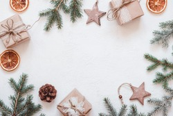 Neutral Christmas frame of fir branches, eco friendly gifts and baubles.
