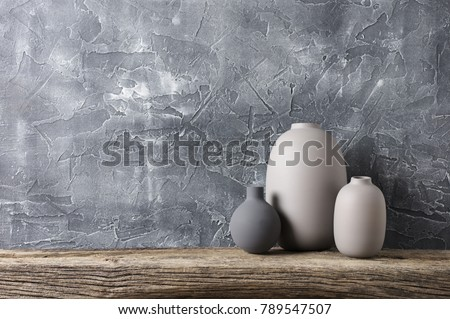 Neutral colored vases on distressed wooden shelf against rough plaster grey wall. Home decor.