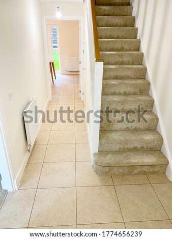 Neutral colour home interior floor tiles and staircase stock photo