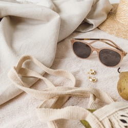 Neutral fashion composition with women's accessories and bijouterie on beige blanket. String bag, straw hat, sunglasses, rings, earrings, pear. Minimal lifestyle concept.