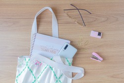 Neutral fashion composition with women's accessories and stationary on wooden table. Cotton bag, stapler, paper clips, glasses, notebook and smartphone . Minimal lifestyle concept.