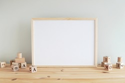 Neutral nursery horizontal frame mockup, empty wooden frame in baby room to showcase artwork, print, photo, painting.