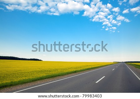 never ending highway through green fields and blue cloudy sky
