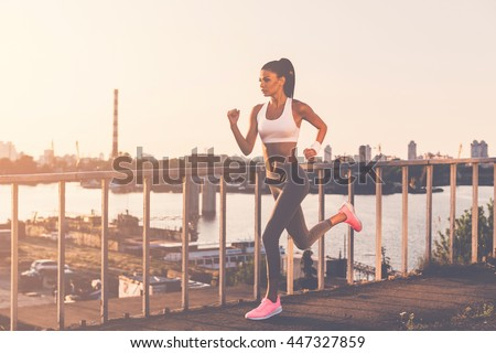 Never give up and keep moving! Full length of beautiful young woman in sports clothing running along the bridge