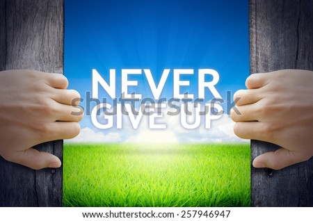 Never Give up. Hand opening an old wooden door and found Never Give up word floating over green field and bright blue Sky Sunrise.