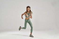 Never stop. Full length shot of young sportive mixed race woman in sportswear looking at camera while running or exercising isolated over grey background. Healthy lifestyle and sport. Vertical shot