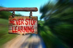 Never stop learning motivational phrase sign on old wood with blurred background
