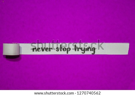 Never stop trying, Inspiration, Motivation and business concept on purple torn paper