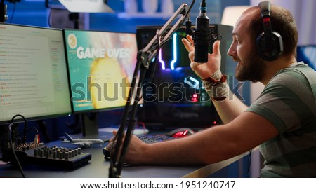 Nevous streamer losing videogame, game over for man cyber playing online space shooter games with headset. Player performing on powerful computer talking with players on chat in gaming competition