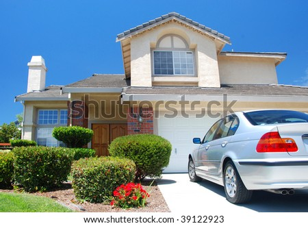 New American dream home with a beautiful blue sky in background and brand new car parked outside
