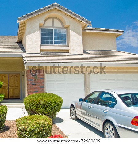 New American dream home with a beautiful blue sky in background and brand new car parked outside.
