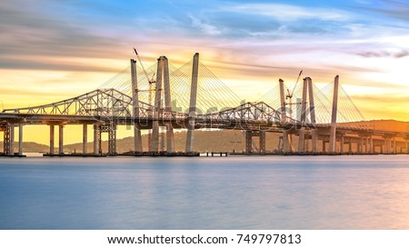 New and Old Tappan Zee Bridges coexisting across Hudson River at sunset. Constructors are currently demolishing the old bridge. Stockfoto ©