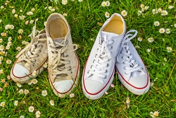 New and old white sneaker chucks shoes. Fashion Shoes Background. Old dirty sneakers vs new white sneakers on green grass background. Trendy footwear.