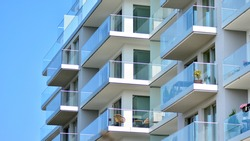 New apartment building with glass balconies. Modern architecture houses by the sea. Large glazing on the facade of the building.