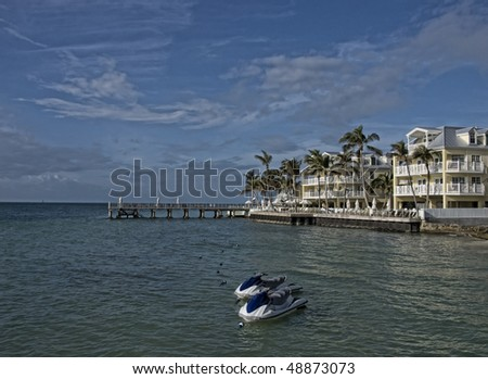 New apartment buildings condominiums on the beach in Key West. There is a pair of water craft waiting for passengers.
