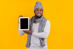 New application or website. Afro man in winter clothes showing blank digital tablet screen, yellow studio background