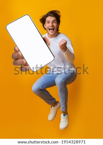 New awesome mobile app. Jumping emotional young guy showing smartphone with blank screen on orange studio background, mockup for application or website design