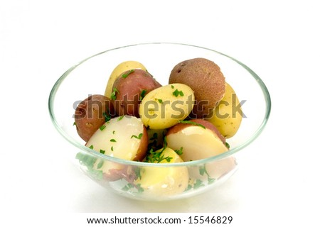 New baby red and gold potatoes with sprinkles of parsley in glass bowl isolated on white