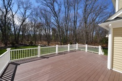 New backyard deck. White vinyl railings and composite brown boards. Large patio and garden space with a view to the woods.