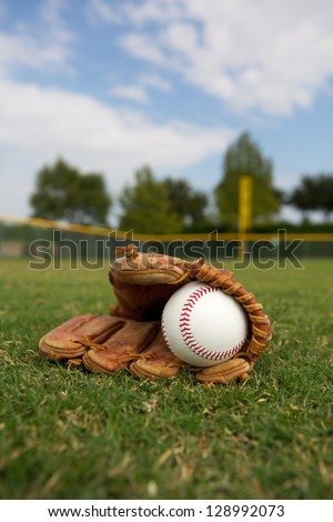 New Baseball in a Glove in the Outfield - stock photo