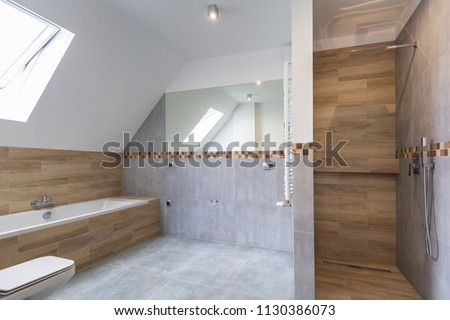 New bathroom interior in the house. Gray concrete tiles with wooden decor. #1130386073