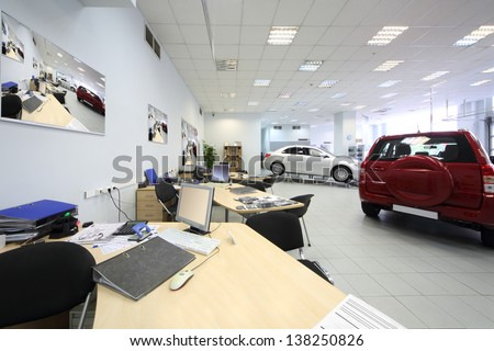 New beautiful cars stand in big office of shop selling cars.