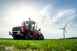 New big red modern farm tractor with quad tracks for powerful combine trailer and ploughing attachments.  Parked in sunshine on farmers rural agricultural field with wind turbine electric generator.