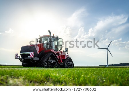 New big red modern farm tractor with quad tracks for powerful combine trailer and ploughing attachments.  Parked in sunshine on farmers rural agricultural field with wind turbine electric generator. Сток-фото ©