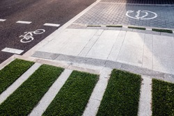 New bike lanes next to recharging stations for electric vehicles on paved asphalt.