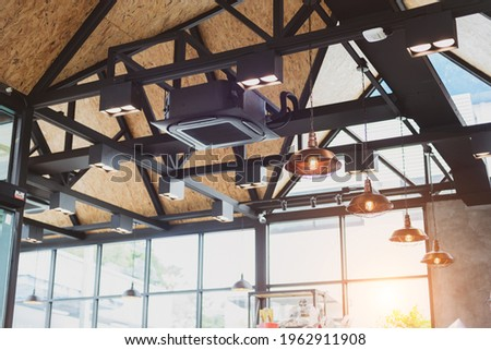New black air conditioning vent on ceiling modern restaurant, inside background. Heavy ceiling air conditioner decoration in loft style office. Cassette type air conditioner with vintage ceiling lamp Photo stock ©