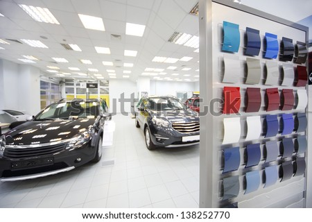 New black cars stand in car shop near stand with samples of paint for body. Focus on stand with samples.