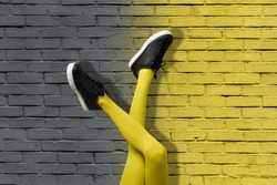 New Black female sneakers on long slender girl legs in yellow tights on background of gradient yellow and gray brick wall. Color of 2021 year pop art concept.